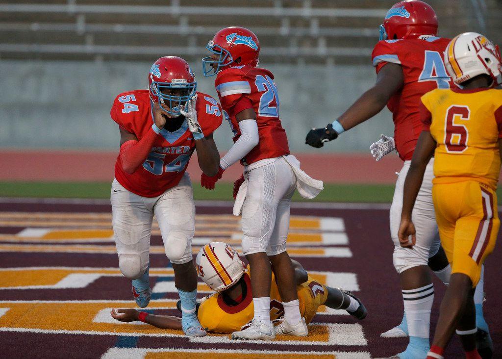 Dallas Carter players Randy Anthony (54) and Jv'Quavion Vinson (20) celebrate their safety on Houston Yates running back Denzel Holmes (23) during the second half of their high school football game in Dallas, Texas on August 31, 2019. (Michael Ainsworth/Special Contributor)