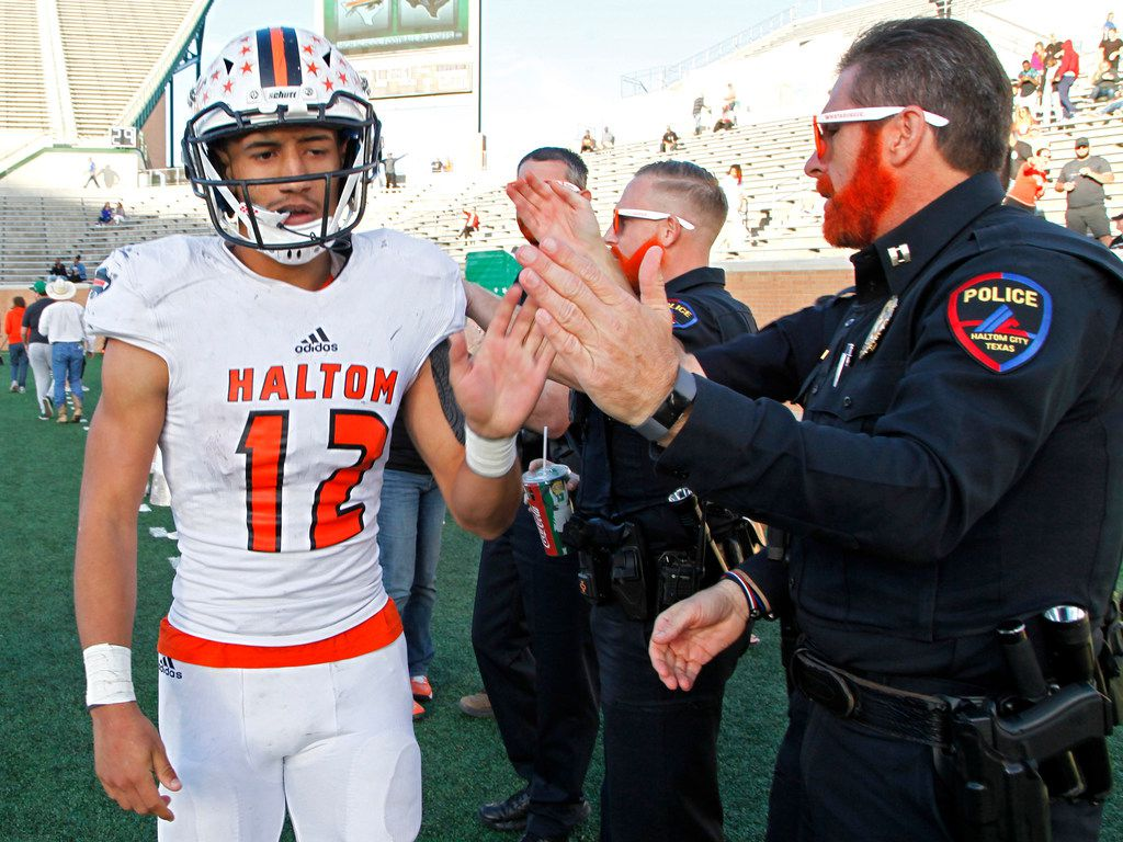 Haltom High School quarterback Michael Black (12) is congratulated by a Haltom City police officer after Black scored a touchdown during the second half as Hebron High School hosted Haltom High School in a Class 6A, Division II, Region 1 semifinal playoff football game at Apogee Stadium in Denton on Saturday, December 1, 2018.  (Stewart F. House/Special Contributor)