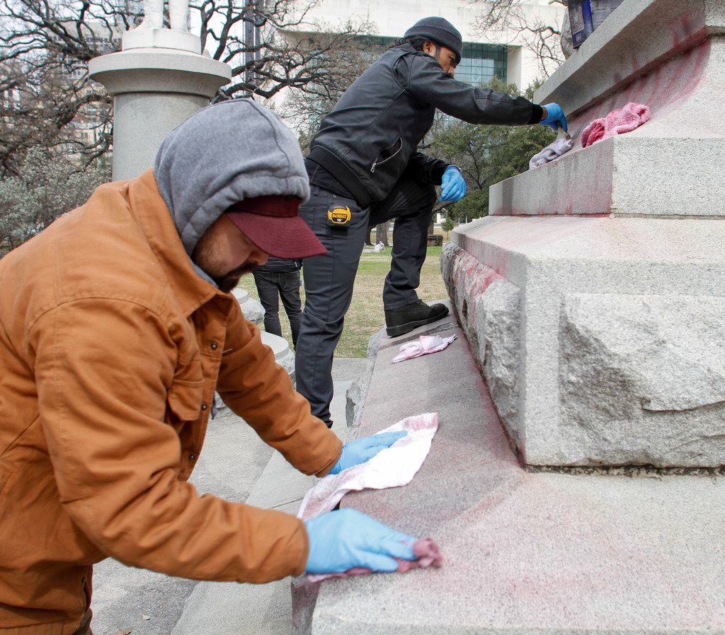 Jorge Meza, left, and Humberto DeGarrio from Bronze Conservation clean graffiti from the Confederate War Memorial monument Monday