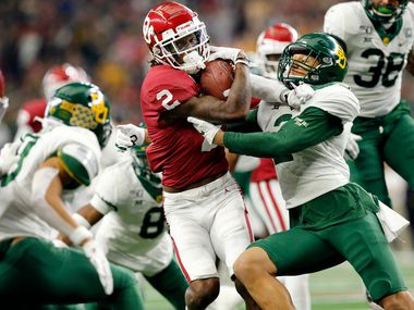 FILE - Oklahoma wide receiver CeeDee Lamb (2) protects the ball as he's tackled a bevy of Baylor defenders, including linebacker Blake Lynch (2), in the fourth quarter of the Big 12 Championship at AT&T Stadium in Arlington on Saturday, Dec. 7, 2019.