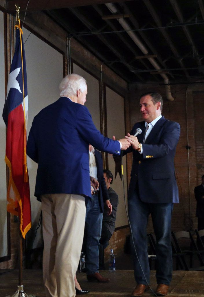 Sen. Ted Cruz (right) takes the microphone from Sen. John Cornyn after Cornyn introduced Cruz  during a rally at Gilley's in Dallas on Oct. 24, 2018.