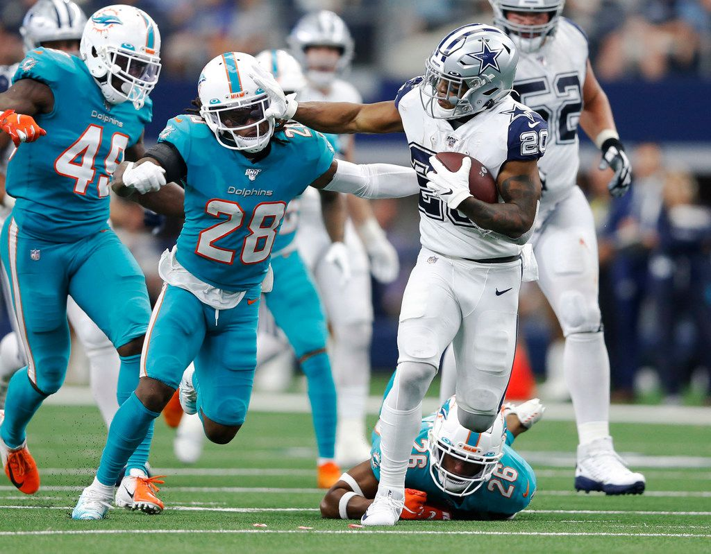 Cowboys running back Tony Pollard (20) tries to break away from Dolphins defensive backs Steven Parker (26) and Bobby McCain (28) during the second half of play at AT&T Stadium in Arlington on Sunday, Sept. 22, 2019.