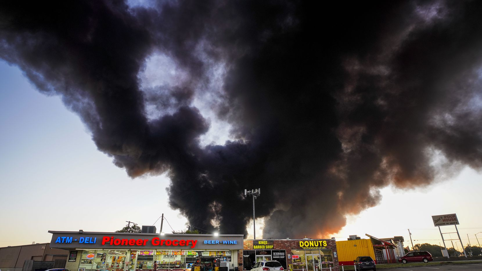 A plume of smoke rises over businesses at the corner of Great Southwest Parkway and Marshall Drive as fire crews battle a massive blaze in an industrial area of Grand Prairie just before sunrise on Wednesday, Aug. 19, 2020.