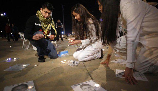 Jaime Santana (izq.), Rosalía Salazar y Liliana Salazar colocan velas sobre fotos de los estudiantes desaparecidos en Ayotzinapa, México, durante una protesta el martes en el puente Continental de Dallas. (DMN/NATHAN HUNSINGER)