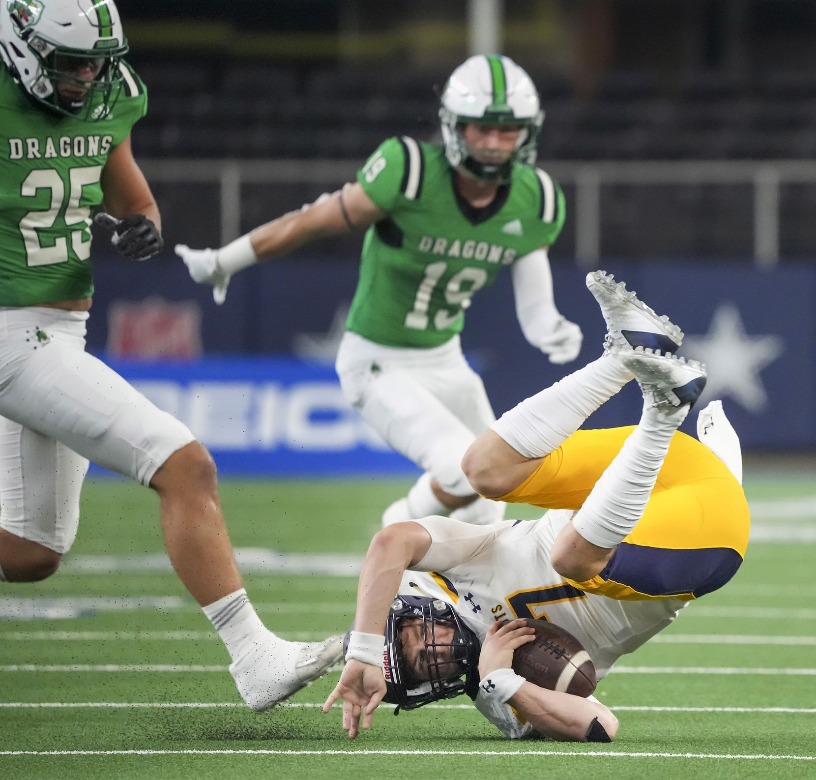 Highland Park quarterback  Brennan Storer (7) tumbles to the turf as he is upended in front of Southlake Carroll defensive lineman Barrett Baker (25) and defensive back Logan Anderson (19) during the first half of a high school football game at AT&T Stadium on Thursday, Aug. 26, 2021, in Arlington.