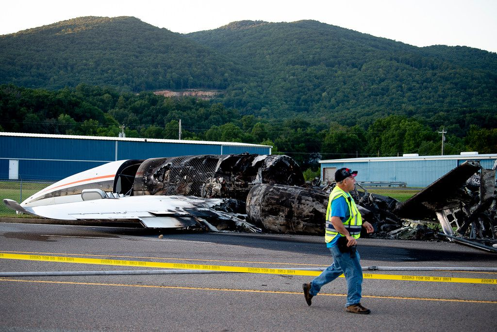 """The burned remains of a plane that was carrying NASCAR television analyst and former driver Dale Earnhardt Jr. lies near a runway Thursday, Aug. 15, 2019, in Elizabethton, Tenn. Officials said the Cessna Citation rolled off the end of a runway and caught fire after landing at Elizabethton Municipal Airport. Earnhardt's sister, Kelley Earnhardt Miller, tweeted that """"everyone is safe and has been taken to the hospital for further evaluation."""" (Calvin Mattheis/Knoxville News Sentinel via AP)"""