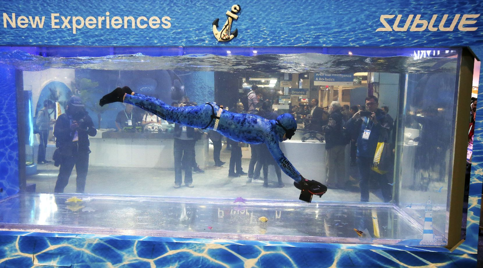 A Sublue diver moves around with the Sublue WhiteShark Mix outfitted with dual propellers for power and balance at a water tank booth during the CES tech show on Wednesday. (AP Photo/Ross D. Franklin)