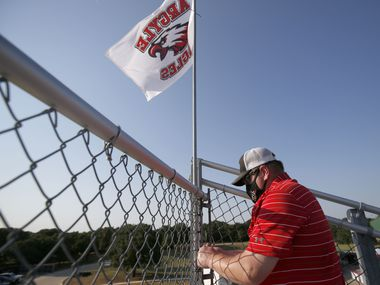 Argyle volunteer Mike Shandley puts flags int the stands prior to the Argyle-Decatur high school football game in Argyle, Tx, on August 28, 2020.