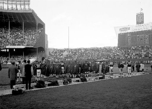 Players and fans at Cleveland Municipal Stadium pause for a moment of silence in honor of President Kennedy, who was assassinated in Dallas, Texas two days earlier, on Friday, Nov. 22.