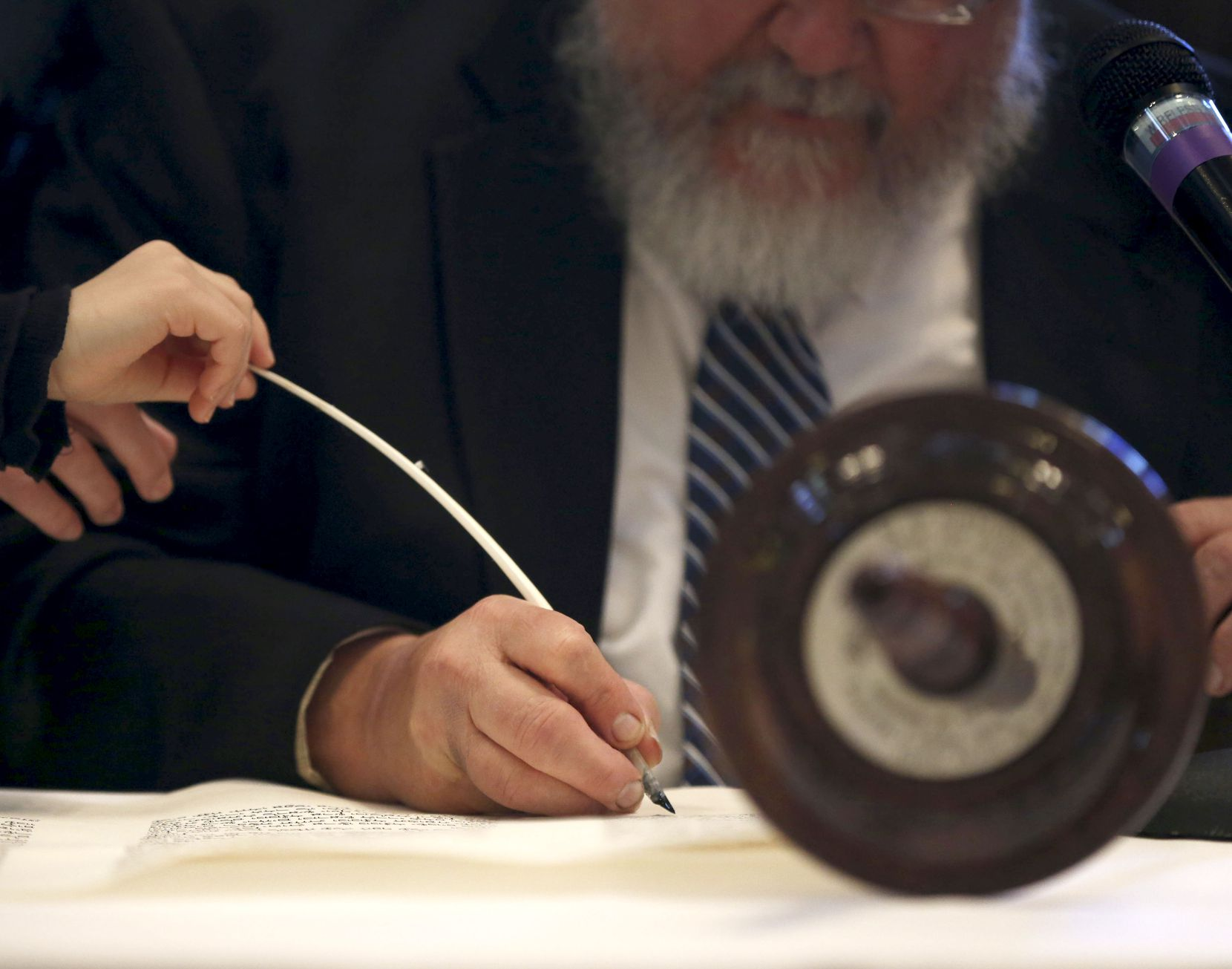 A child holds the end of the scribe's quill as he writes as a way to participate in the completion of a torah at Congregation Anshai Torah to honor Wende Weinberg, the synagogue's beloved teacher and wife of its rabbi.