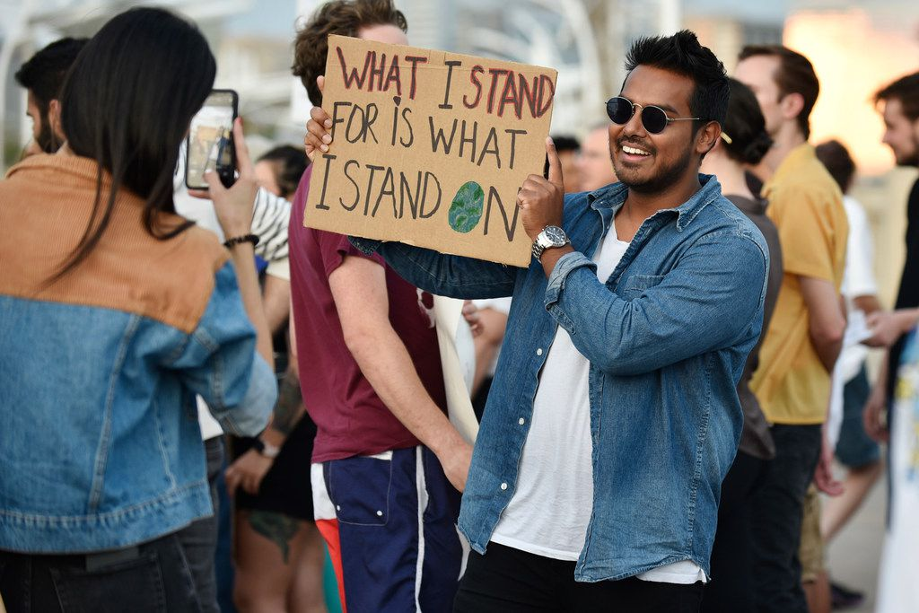 Rayyan Islam, 28, of Allen, smiles for a photo while holding his pro-Earth sign before the start of the Global Climate Strike rally near the Margaret Hunt Hill Bridge in Dallas, Sept. 20, 2019.