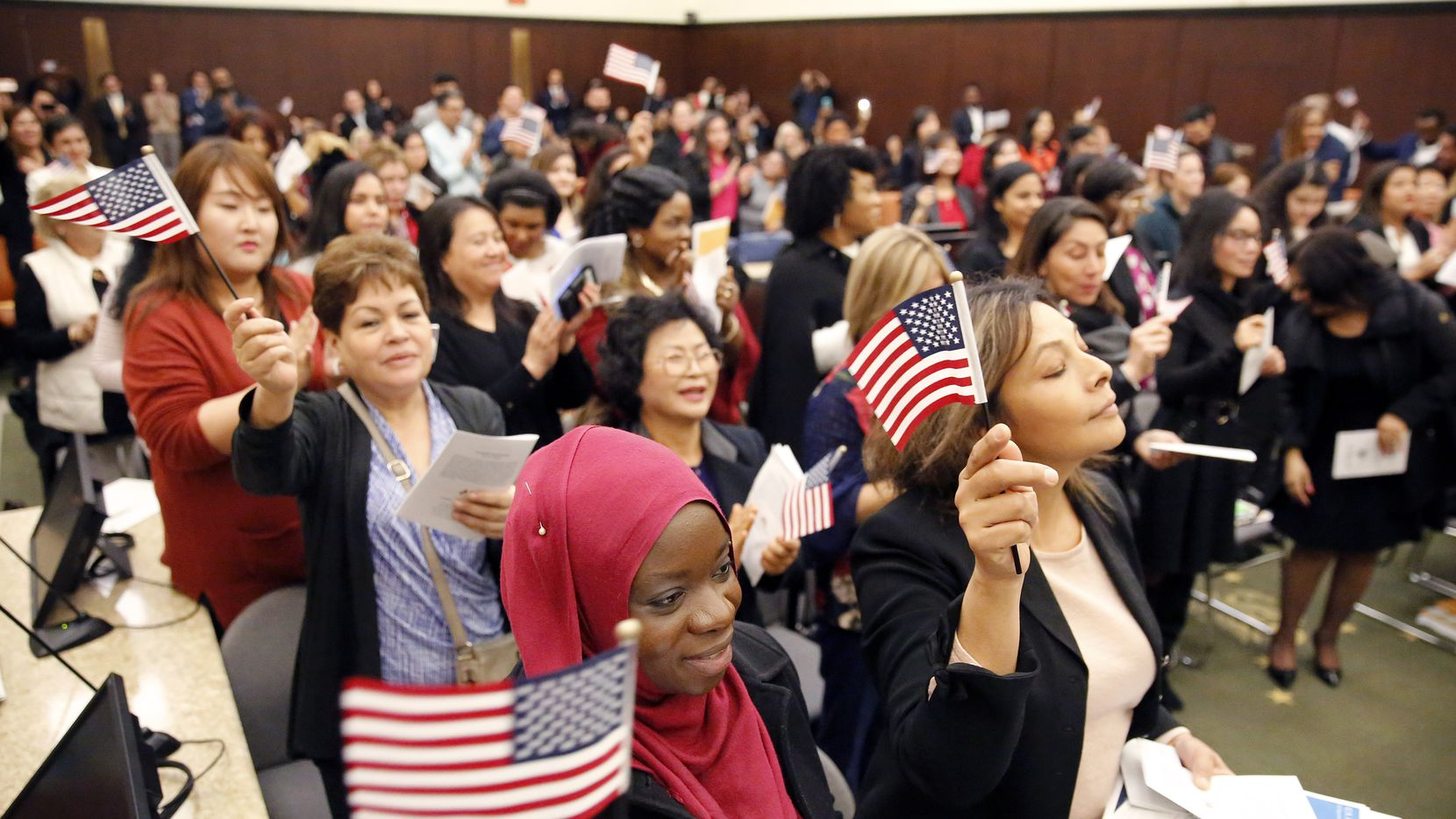 Fatimah Oritola of Nigeria (foreground) of Nigeria and others wave U.S. flags after reciting the oath of allegiance led by US Chief District Judge Barbara Lynn during a naturalization ceremony at the Earle Cabell Federal Building in Dallas, Wednesday, December 19, 2018.