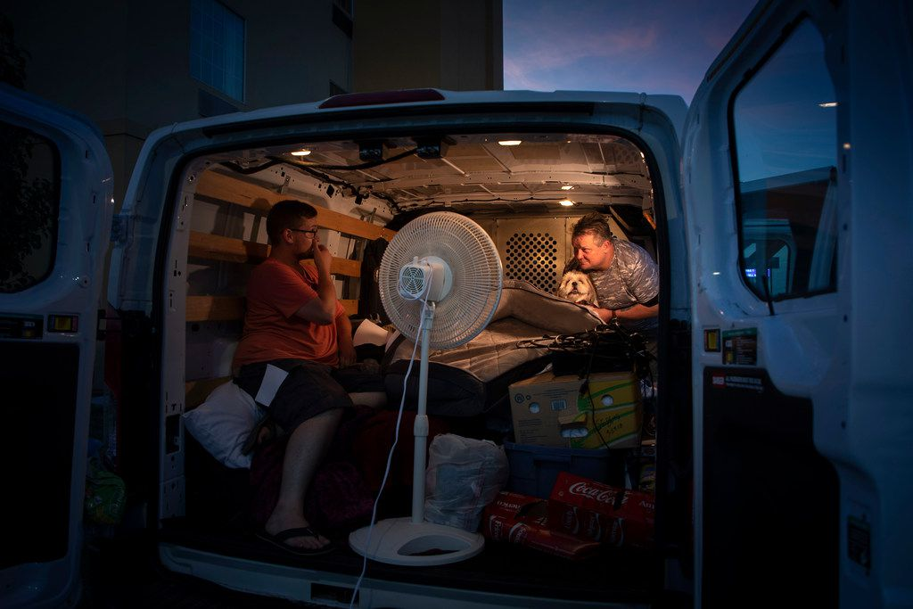 Jeff Slaughter (right) talks with his son, Cameron, in the back of a U-Haul van  Wednesday in Denton. Slaughter says he wants answers after his monthly disability check didn't show up in his bank account earlier this month.