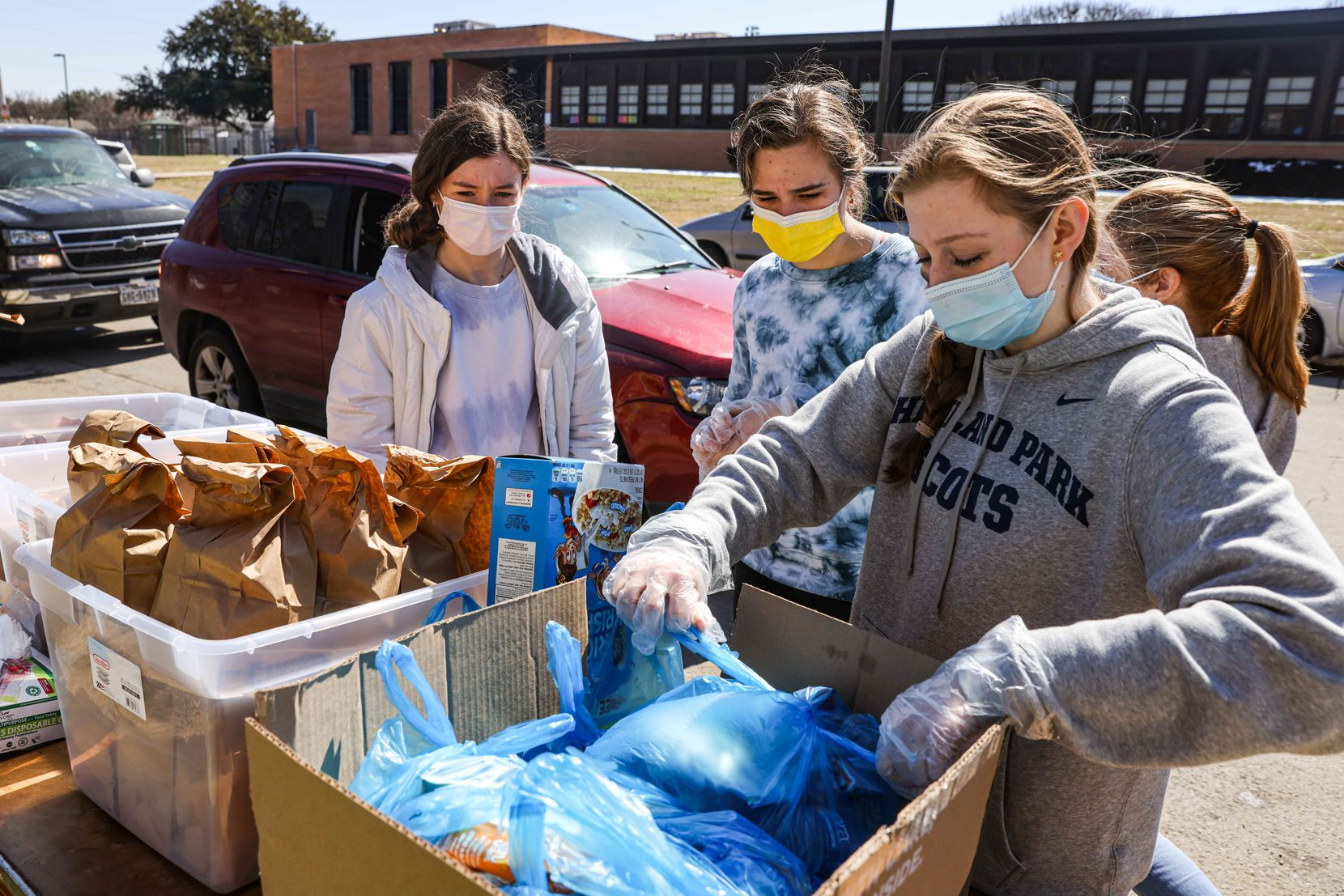 From left, volunteers Ellie Donahoe, 15, Caroline Vallard, 15, and Jullian Miller, 15, distribute food aid to the community at Ledbetter food pantry in Iglesia El Calvario as temperatures start to rise and the snow accumulated after the passage of snowstorm Uri begins to melt in Dallas on Friday, February 19, 2021. (Lola Gomez/The Dallas Morning News)