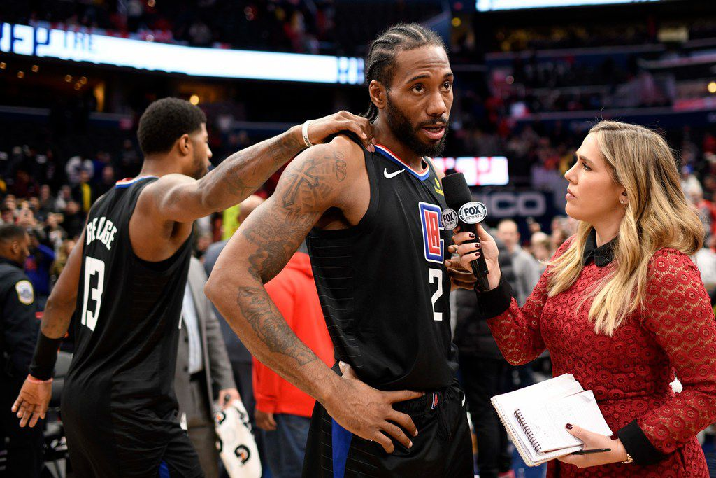 Los Angeles Clippers forward Kawhi Leonard (2) is interviewed by Jaime Maggio, right, after an NBA basketball game Washington Wizards as forward Paul George (13) passes by, Sunday, Dec. 8, 2019, in Washington. The Clippers won 135-119. (AP Photo/Nick Wass)