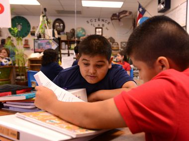 Students Jose Saavedra (left) and Ulisses Salto read an assignment at Brandenburg Elementary in Irving ISD. The school district will implement numerous safety protocols for COVID-19 when welcoming back students and staff to school in August.
