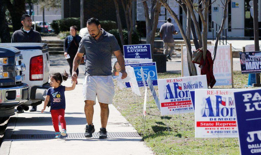 Armando Vergara walks his daughter Evylin, 3, past the Dallas County Government Center, Precinct 5 in Oak Cliff on Election Day,  March 6, 2018. (David Woo/The Dallas Morning News)