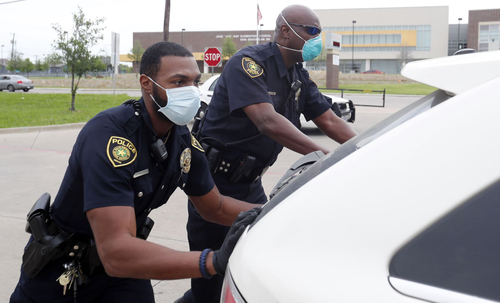 Dallas ISD police Officers Mylon Taylor (left) and Gary Pierre pushed a car that ran out of gas while waiting in line for a weekly school meal handout April 9.
