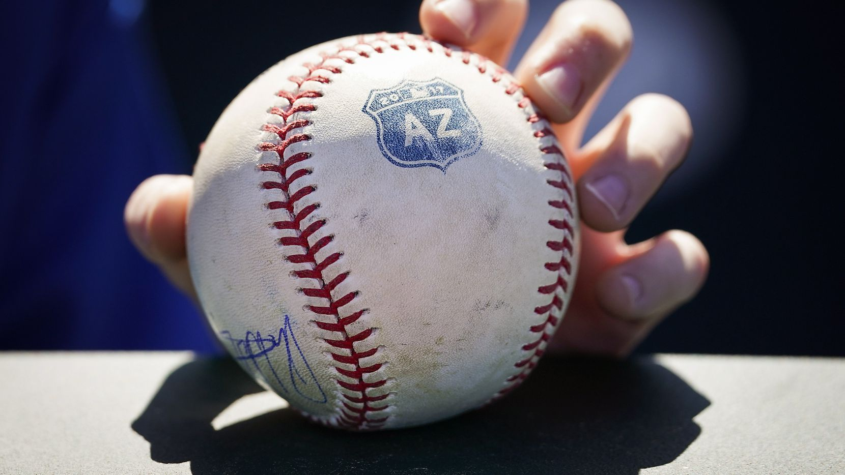 A Texas Rangers fan holds a ball hoping for autographs before a spring training game against the Cincinnati Reds at Goodyear Ballpark  on Monday, Feb. 24, 2020, in Goodyear, Ariz.