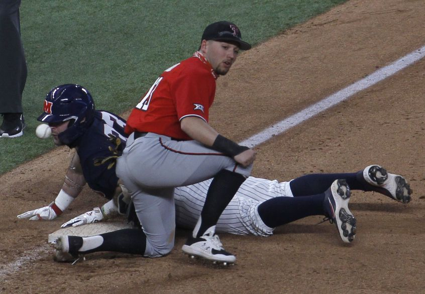 Texas Tech 3rd baseman Cal Conley (13) looks for the ball as a sliding Ben Van Cleve (33) found himself close enough to count the stitches during the bottom of the 3rd inning of play. Van Cleve was safe at 3rd after advancing on an overthrow on the play. Texas Tech played Ole Miss in conjunction with the State Farm College Baseball Showdown tournament held at Globe Life Field in Arlington on February 21, 2021. (Steve Hamm/ Special Contributor)