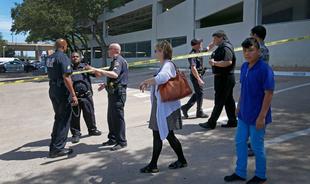 Dallas Police Department officers help workers outside an office building in Lake Highlands near the High Five where police found two people dead at a shooting scene in Dallas, Monday, April 24, 2017. (Jae S. Lee/The Dallas Morning News)