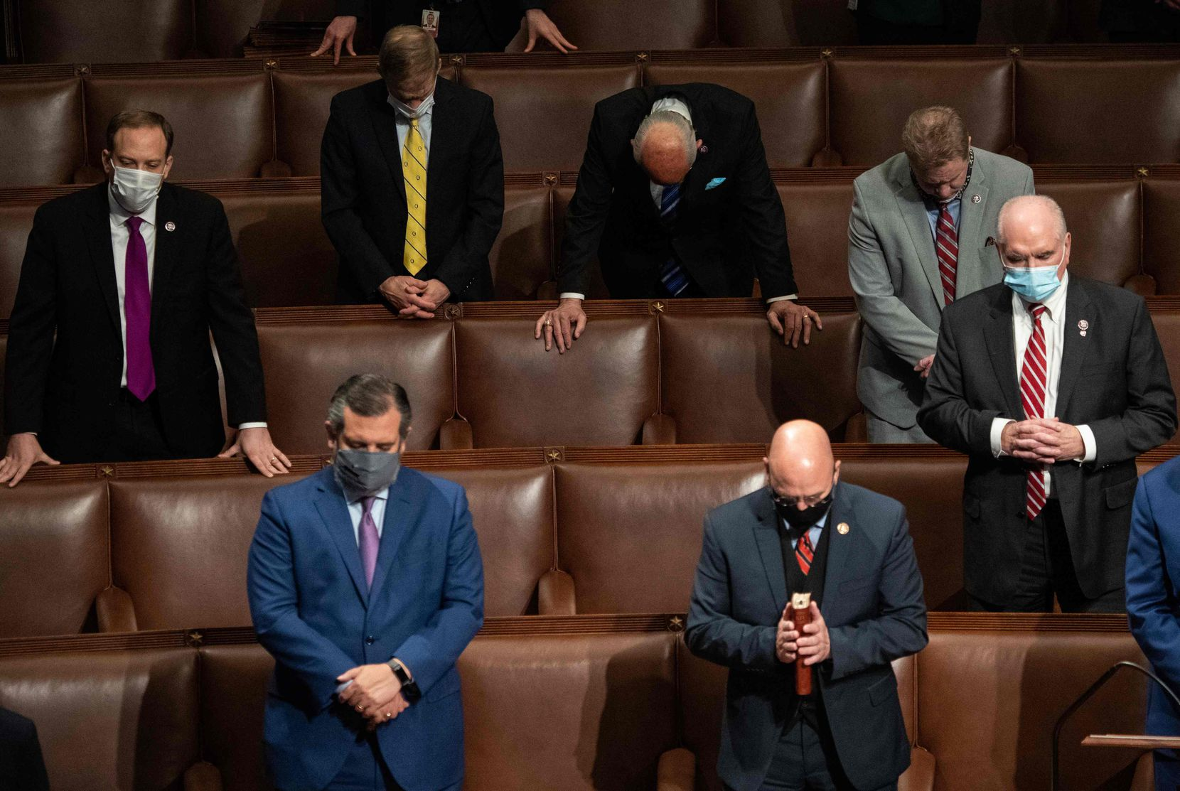 Sen. Ted Cruz and other members of Congress pray after Vice President Mike Pence declared the final electoral vote counts making Joe Biden the next president, early Jan. 7, 2021. Trump supporters interrupted the joint session of Congress when they stormed the Capitol.