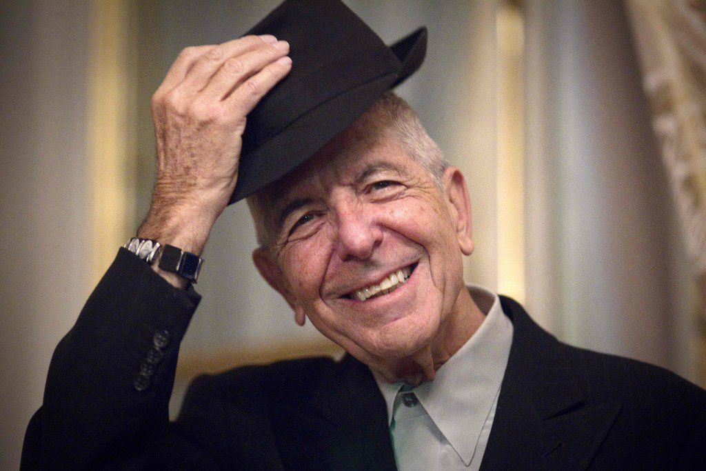 """This photo taken on January 16, 2012, shows Canadian singer and poet Leonard Cohen taking off his hat to salute in Paris.  Leonard Cohen, one of his generation's most respected musicians and poets who delved into the spiritual on songs such as """"Hallelujah,"""" has died at age 82, it was announced on November 11, 2016."""