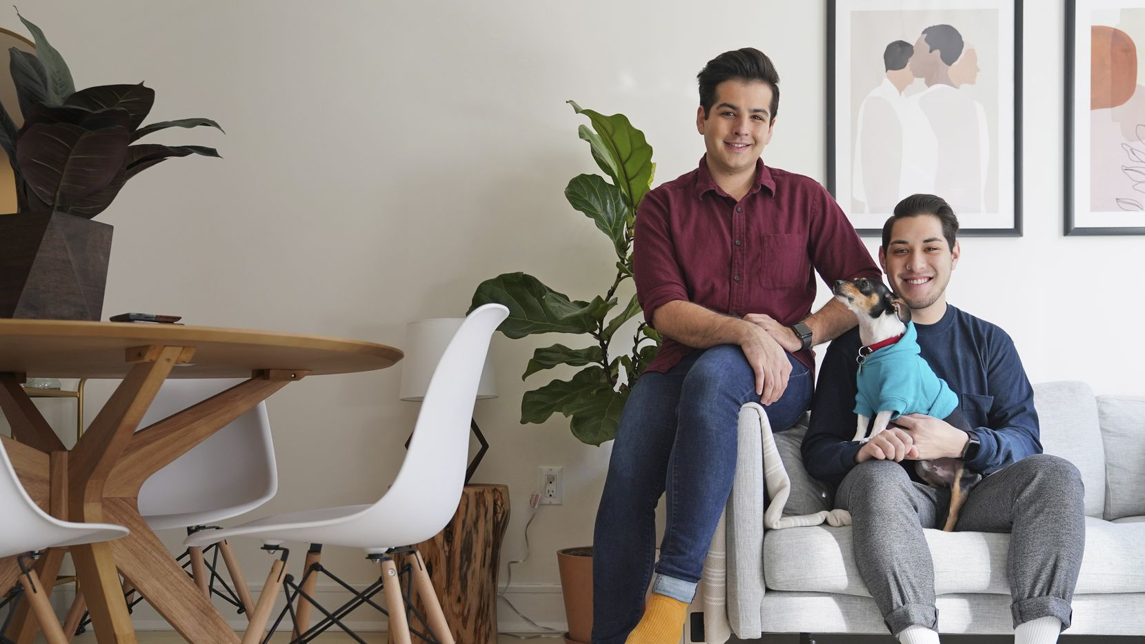 Zachariah Mohammed (left), Pete Mancilla and their dog Remy pose for a picture in their apartment in New York. Most of the furniture in their apartment, including the couch, the table and chairs, the side table and the bar cart, are rented. (AP Photo/Seth Wenig)
