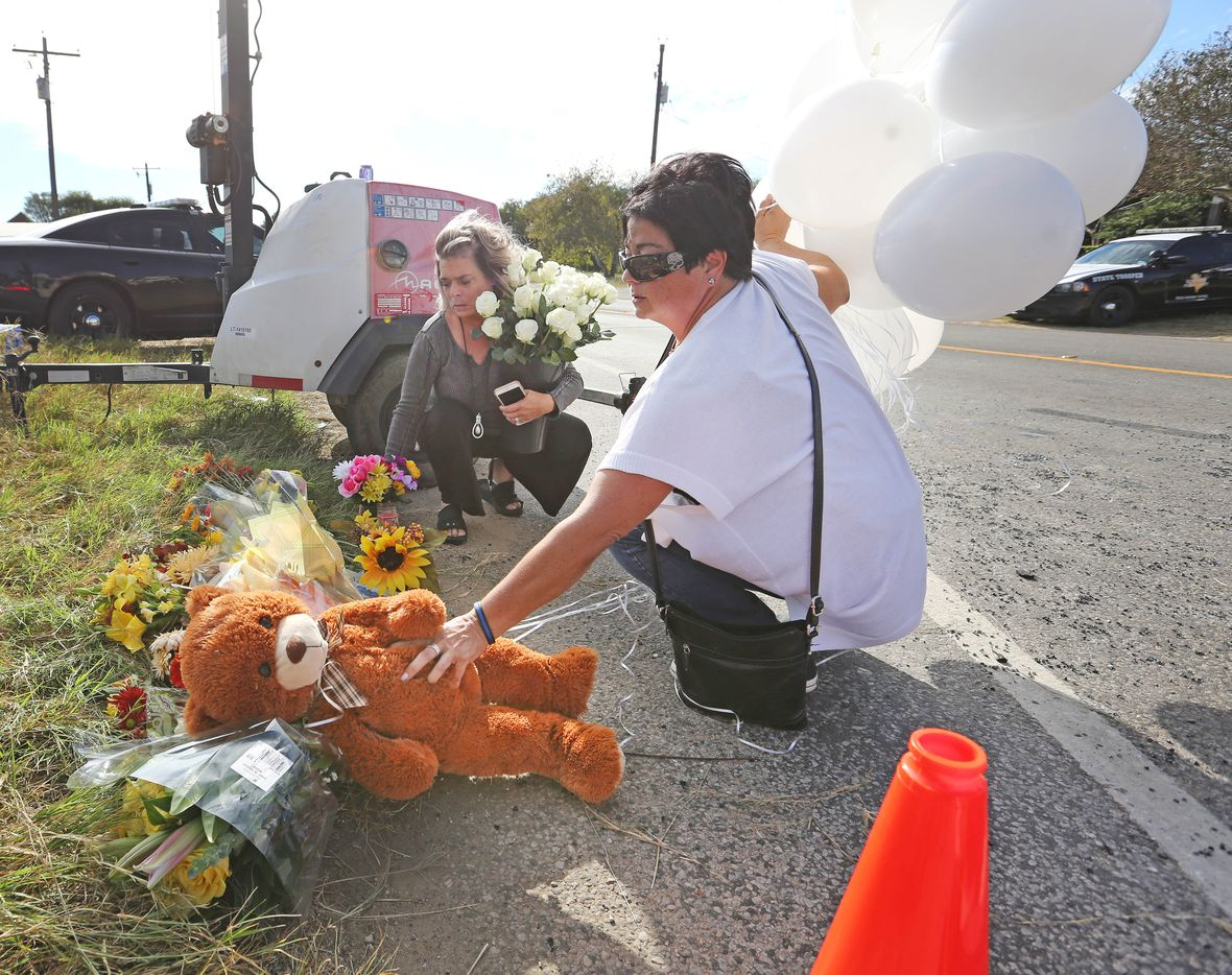 Michelle Trigo, right, and Malinda Lamford, left, of San Antonio deliver 26 balloons, flowers, and a stuffed teddy bear to the First Baptist Church of Sutherland Springs in Sutherland Springs, Texas. At least 26 people died Sunday after a gunman opened fire at a Baptist church in the small town southeast of San Antonio. Photographed on Monday, November 6, 2017. (Louis DeLuca/The Dallas Morning News)