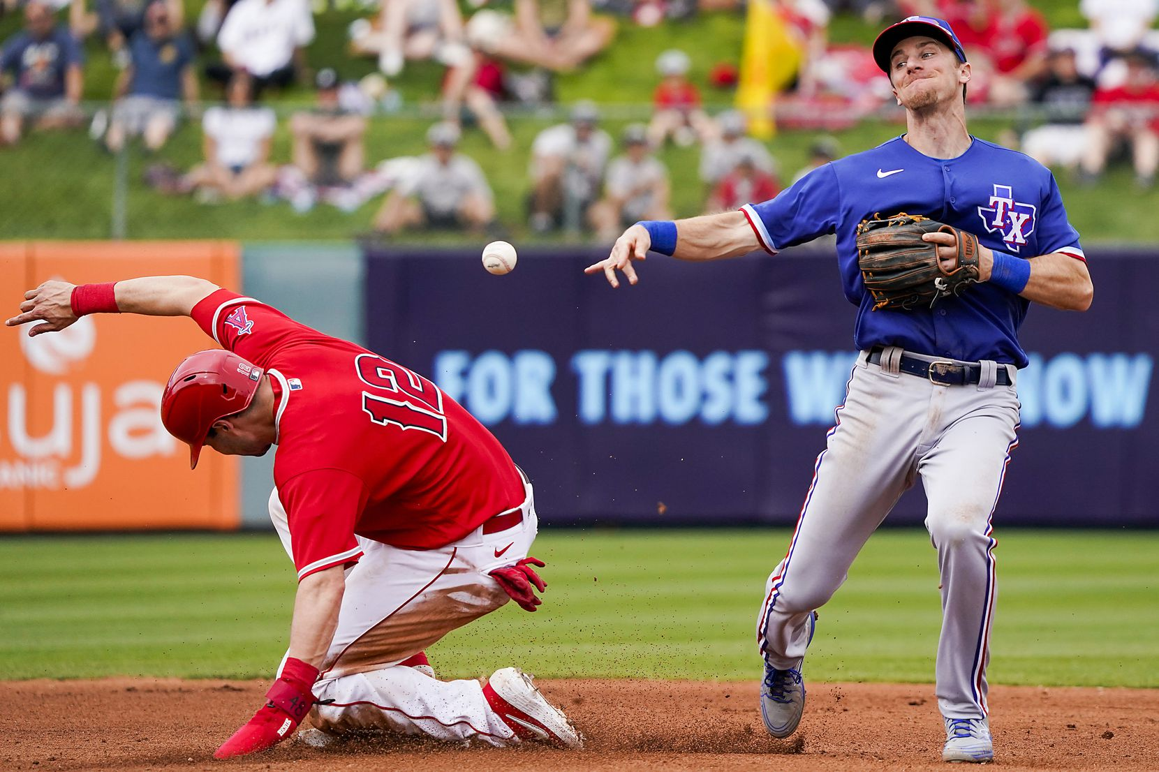 Texas Rangers shortstop Matt Duffy makes the relay over Los Angeles Angels catcher Anthony Bemboom trying to turn a double play during the fourth inning of a spring training game at Tempe Diablo Stadium on Friday, Feb. 28, 2020, in Tempe, Ariz.