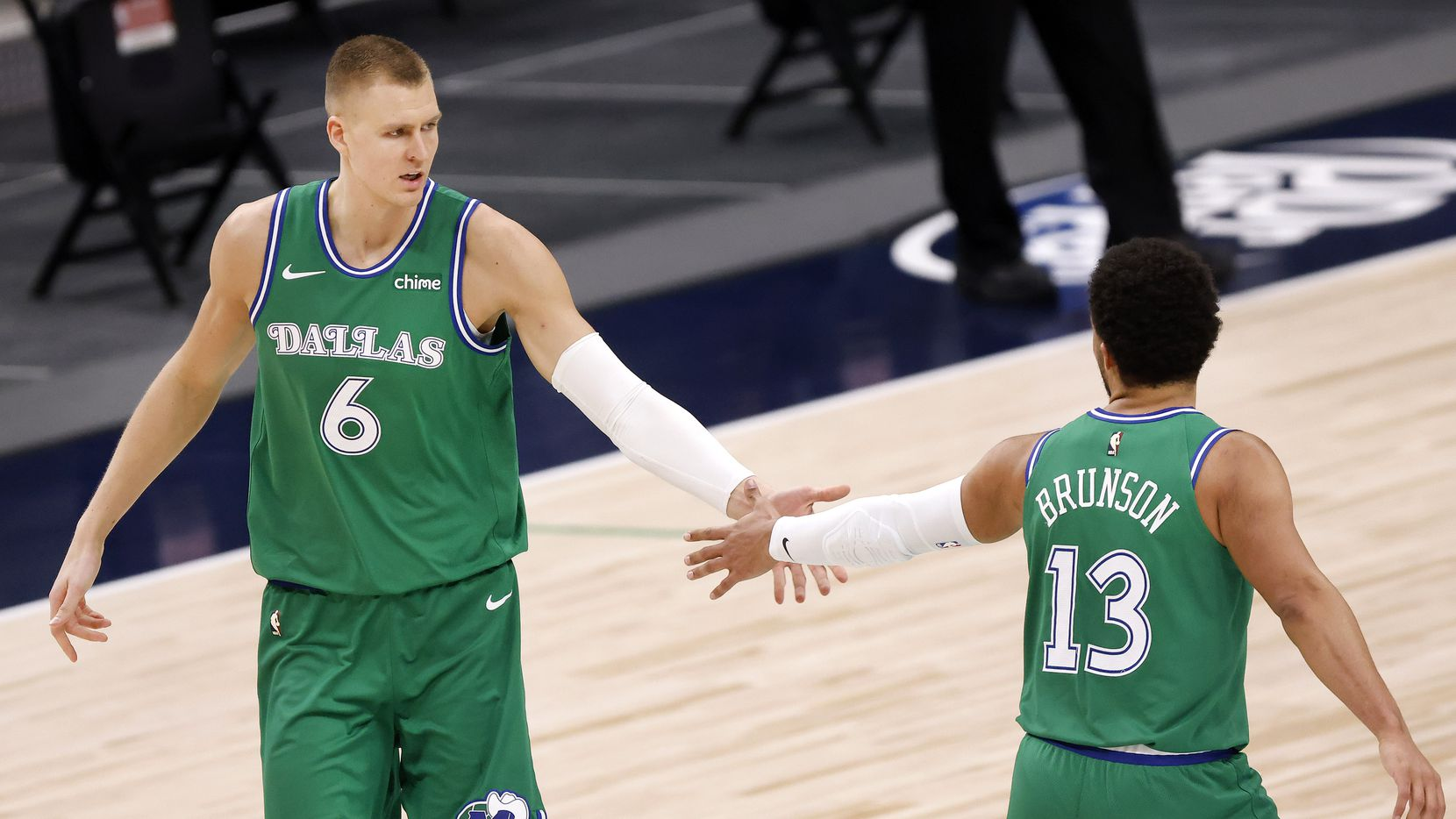 Mavericks center Kristaps Porzingis (6) is congratulated by teammate Jalen Brunson (13) after making a 3-pointer against the Thunder at American Airlines Center in Dallas on Wednesday, March 3, 2021.