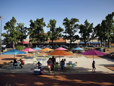 People find shade from the sun in Garland City Square in downtown Garland, Texas, Friday, June 26, 2020.