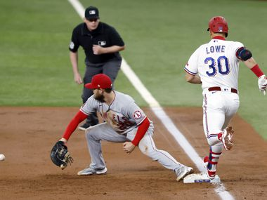 Texas Rangers first baseman Nate Lowe (30) is safe at first as Los Angeles Angels first baseman Jared Walsh (20) scoops up a throw in the first inning at Globe Life Field in Arlington, Texas, Wednesday, April  28, 2021. The play scored Nick Solak. (Tom Fox/The Dallas Morning News)