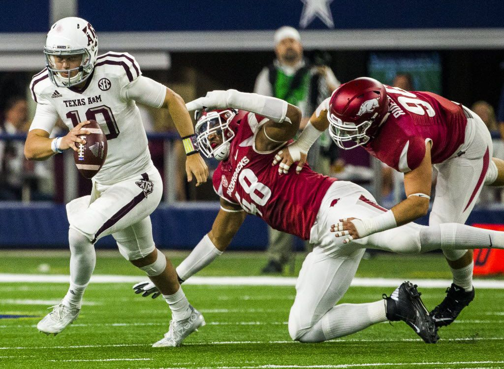 Texas A&M Aggies quarterback Kyle Allen (10) escapes a sack by Arkansas Razorbacks defensive lineman Deatrich Wise Jr. (48) and Arkansas Razorbacks defensive lineman Karl Roesler (96) during the fourth quarter of their game on Saturday, September 26, 2015 at AT&T Stadium in Arlington, Texas.   (Ashley Landis/The Dallas Morning News)