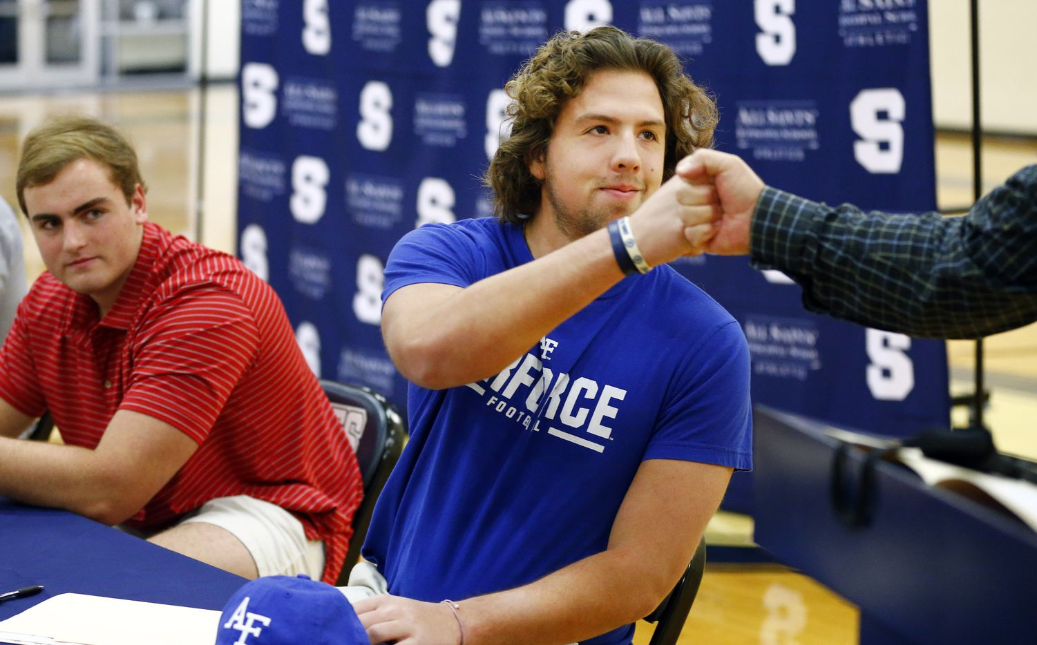 Fort Worth All Saints' Episcopal School football player Paul Breedlove receives a fist bump from head coach Aaron Beck after signing a letter of intent to play at Air Force during an event in the schools gymnasium, Wednesday, December 16, 2020. (Tom Fox/The Dallas Morning News)