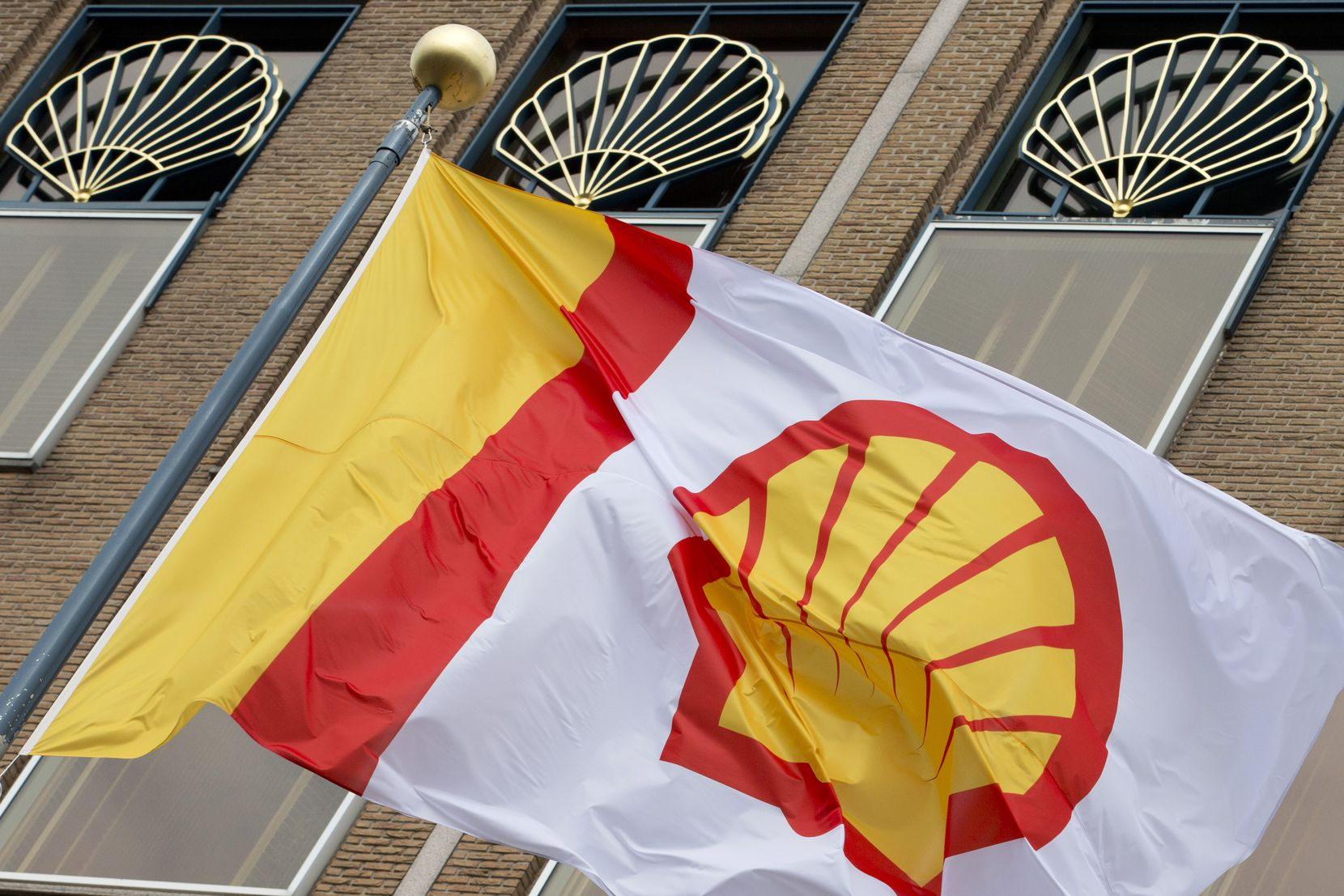 A flag bearing the company logo of Royal Dutch Shell, an Anglo-Dutch oil and gas company, flies outside the head office in The Hague, Netherlands. Royal Dutch Shell will reduce its operating costs by between $3 billion to $4 billion for the next 12 months to adapt to the virus outbreak crisis and plunging oil prices.