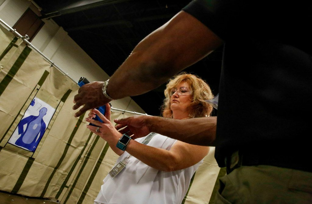 Kim Steinman of Fort Worth gets a lesson on holding a handgun at a Personal Protection Expo held at the Fort Worth Convention Center.