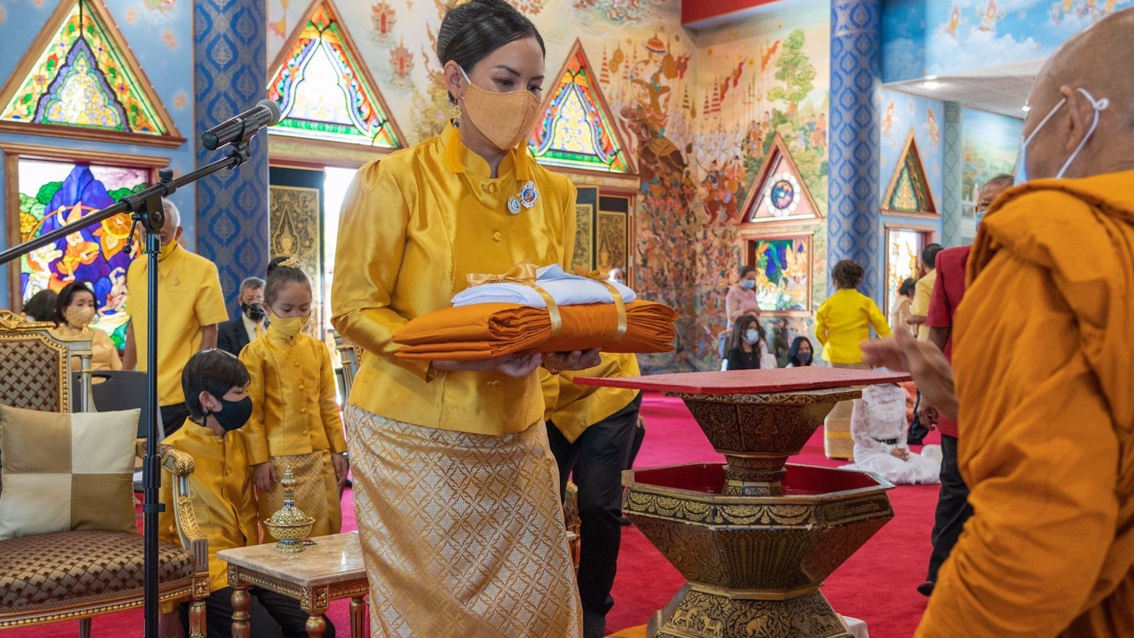 At the Royal Kathina, Nikky Phinyawatana presents a robe blessed in Thailand by King Rama X to The Dallas Buddhist Temple.