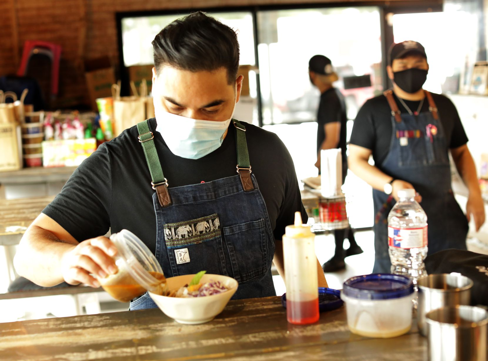 Donny Sirisavath, left, prepares the Khao Poon at Khao Noodle Shop in Dallas