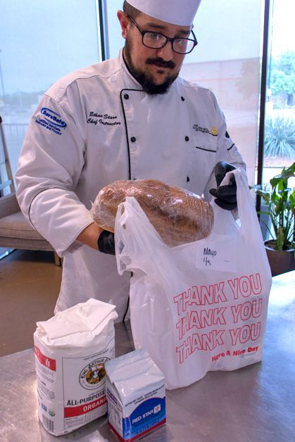 Chef Ethan Starr bags some of the Culinary School of Fort Worth's freshly baked bread for a customer, along with a 5-pound sack of flour and a 1-pound bag of yeast.