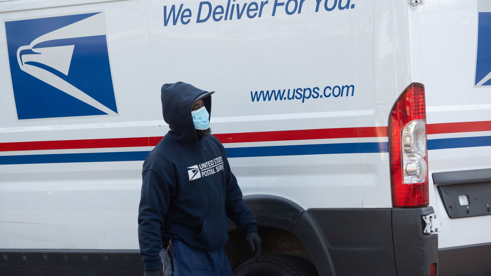 A postal worker wearing a mask and gloves to protect himself and others from COVID-19 loads packages at a Postal Service facility in Washington, DC, April 16, 2020.