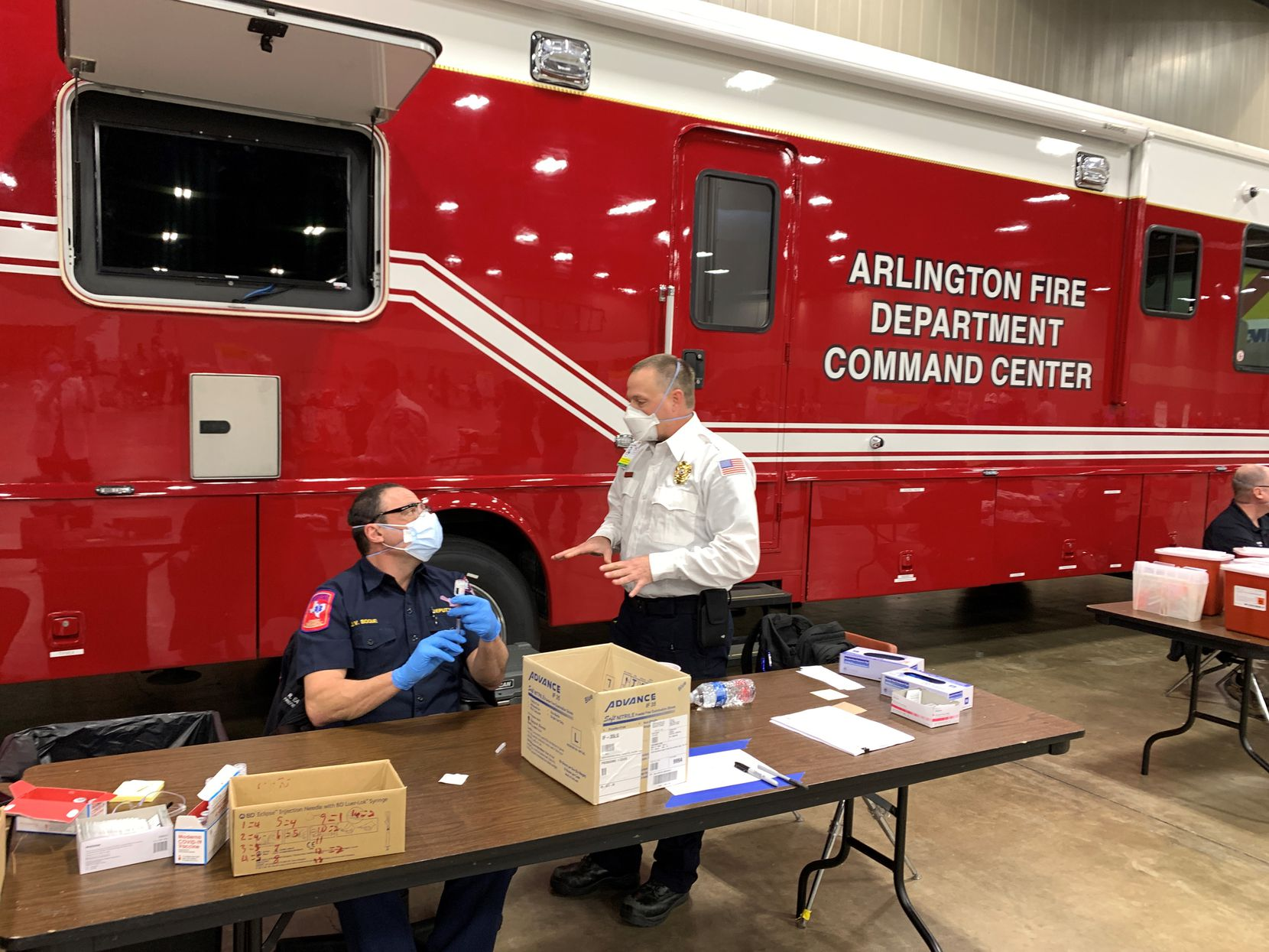Michael Marsh, operations manger at American Medical Response Arlington, and James Boque, Arlington Fire Department Deputy Chief, chat about the vaccine at Arlington's COVID-19 vaccination site. Marsh was deployed to New York City for 30 days last year to help deliver ambulances to first responders.