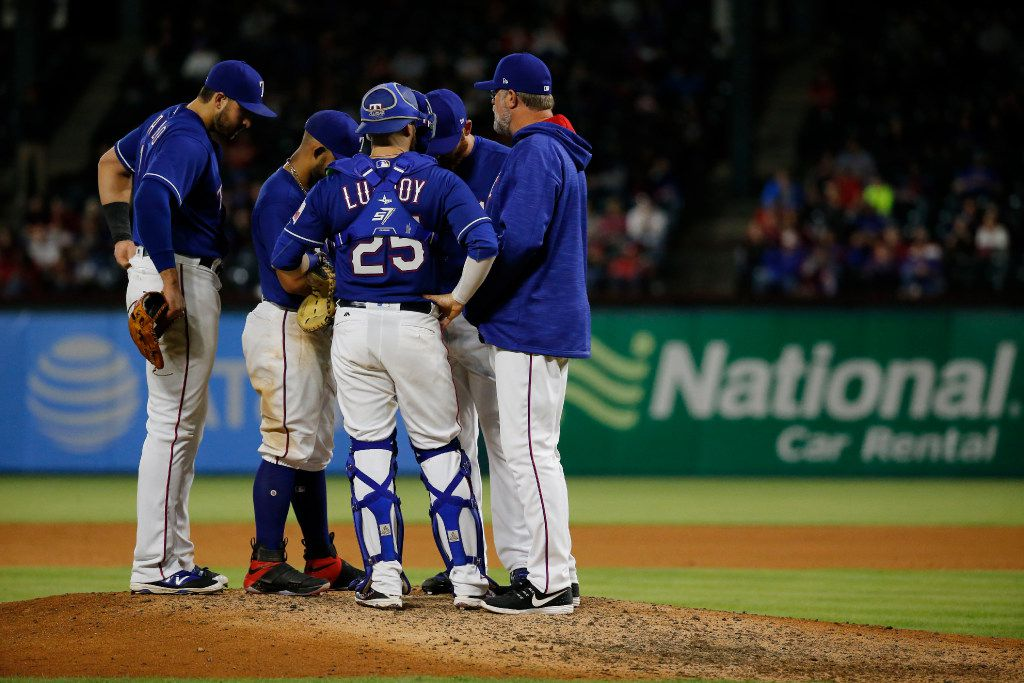 Rangers pitching coach Doug Brocail (far right) approaches the pitching mound to talk to reliever Sam Dyson (47) in the ninth inning against the Cleveland Indians at Globe Life Park on April 5, 2017.