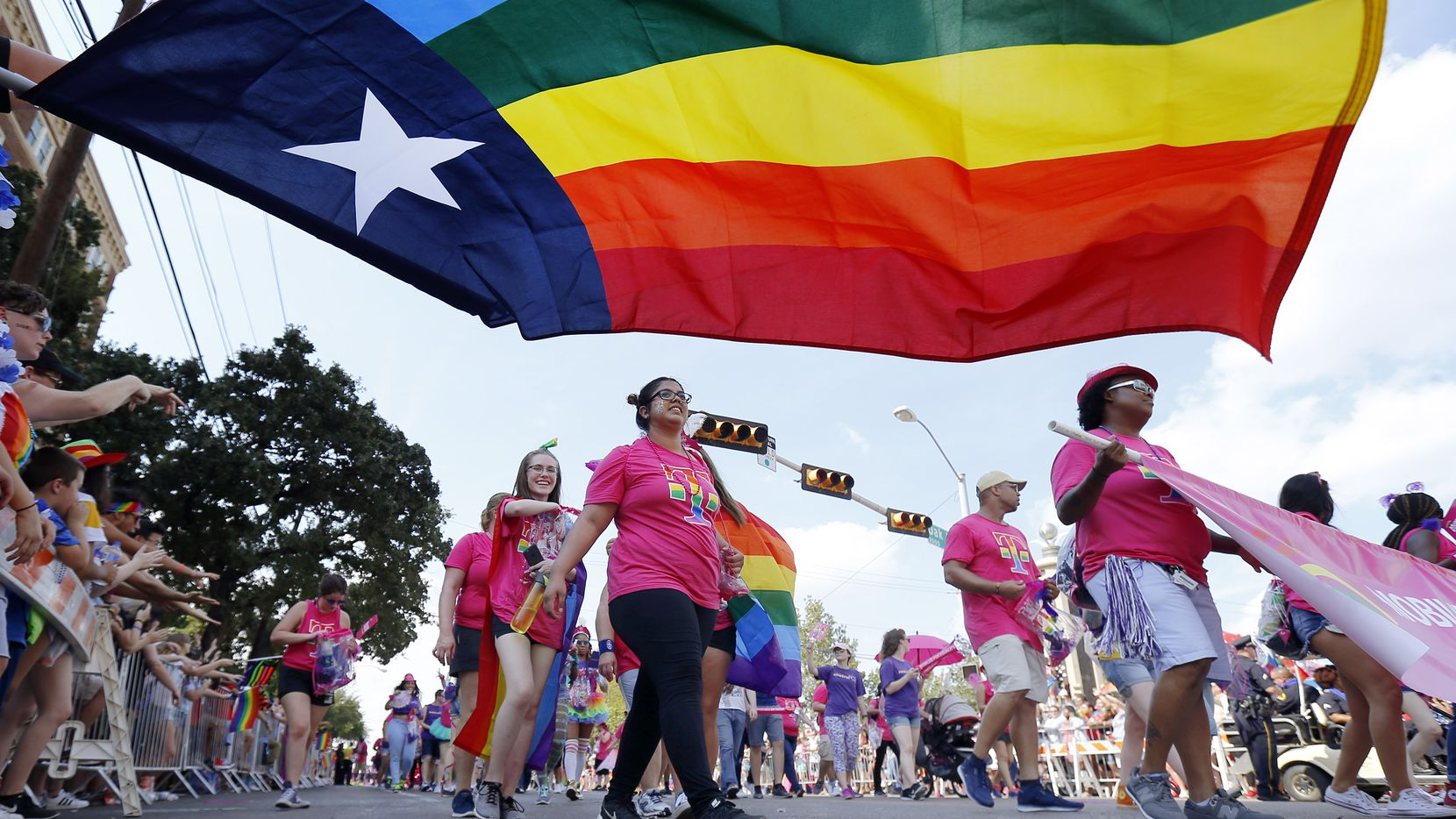 People marching with the Mobilize for Equality group pass by the Texas rainbow flag during the Texas Freedom Parade, Sunday, September 17, 2017.