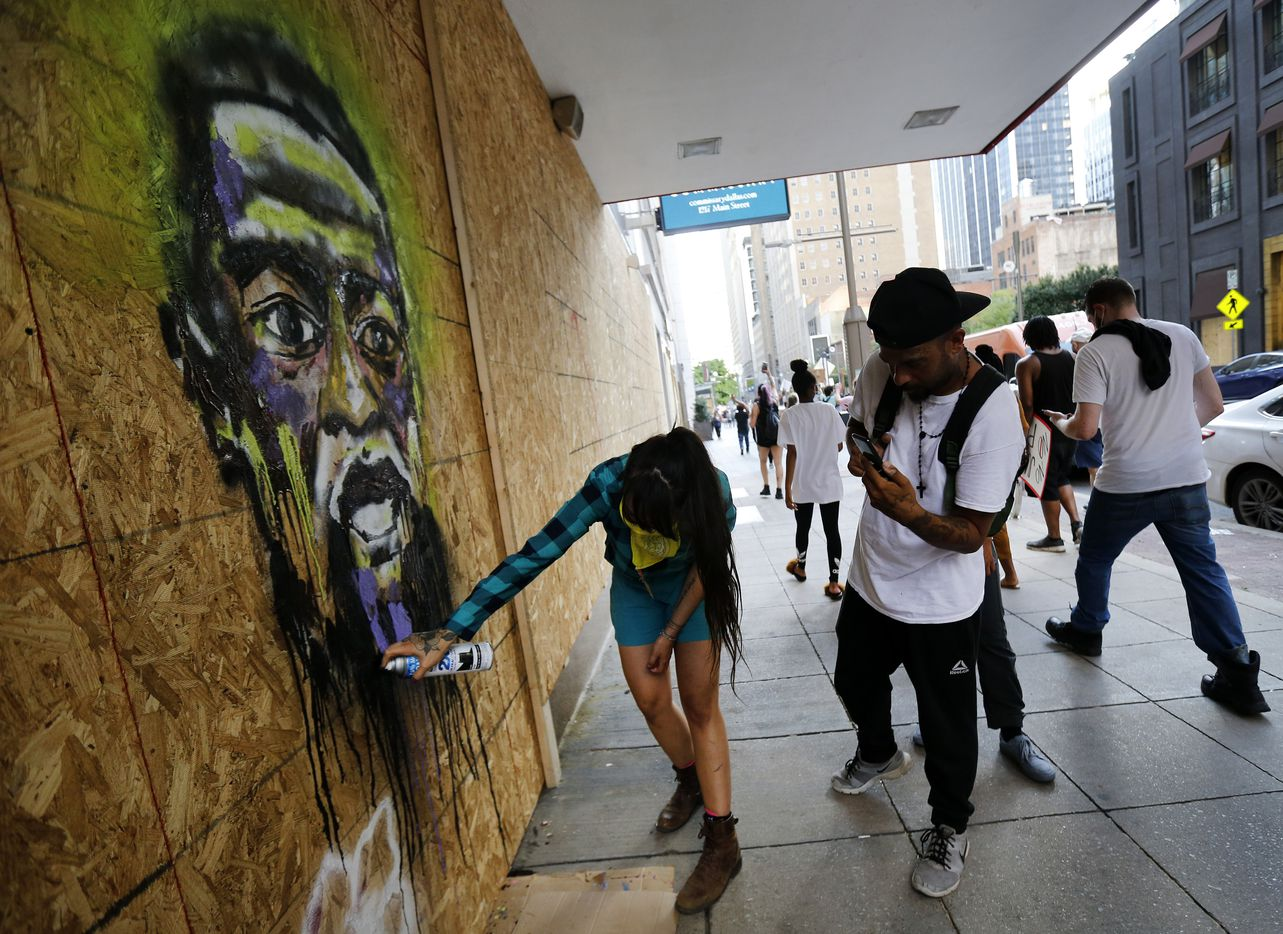 Artist Karla Ceballos spray paints a portrait of George Floyd on the boarded up Neiman Marcus store in downtown Dallas, Friday, June 5, 2020. Protestors supporting Black Lives Matters marched down Main St. as they headed to Dallas City Hall. They marched to protest the in-custody death of George Floyd by a Minneapolis police officer.