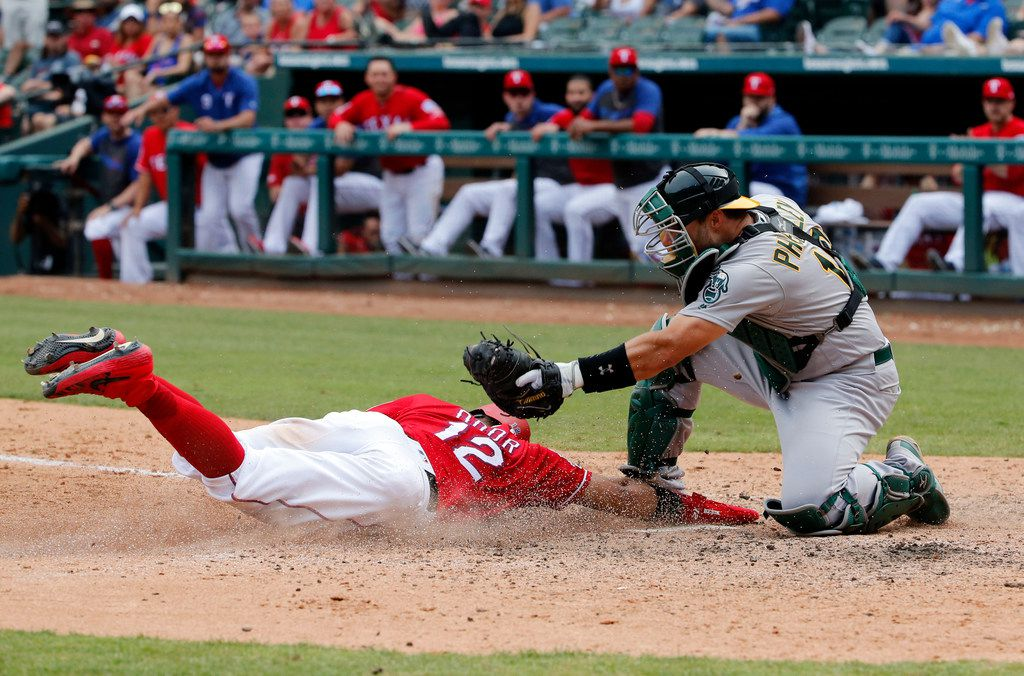 Texas Rangers Rougned Odor (12) steals home as Oakland Athletics catcher Josh Phegley (19) tries to defend the plate during the eighth inning of a baseball game, Sunday, June 9, 2019, in Arlington, Texas. (AP Photo/Michael Ainsworth)