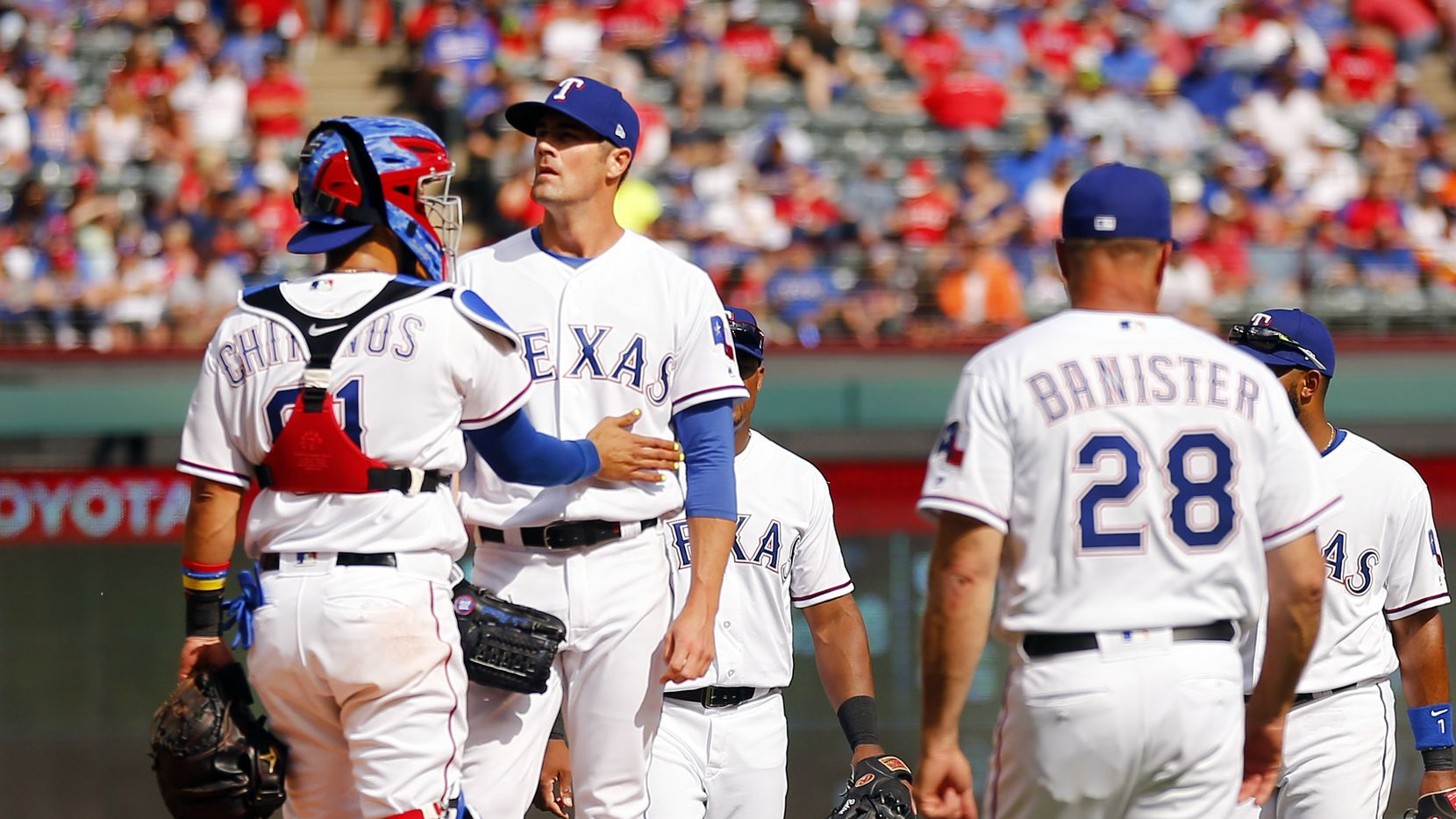 Texas Rangers catcher Robinson Chirinos pats starting pitcher Cole Hamels on the side as manager Jeff Banister (28) comes to pull him in the sixth inning of their Opening Day game against the Houston Astros at Globe Life Park in Arlington, Texas, Thursday, March 29, 2018. The Astros defeated the Rangers, 4-1. (Tom Fox/The Dallas Morning News)