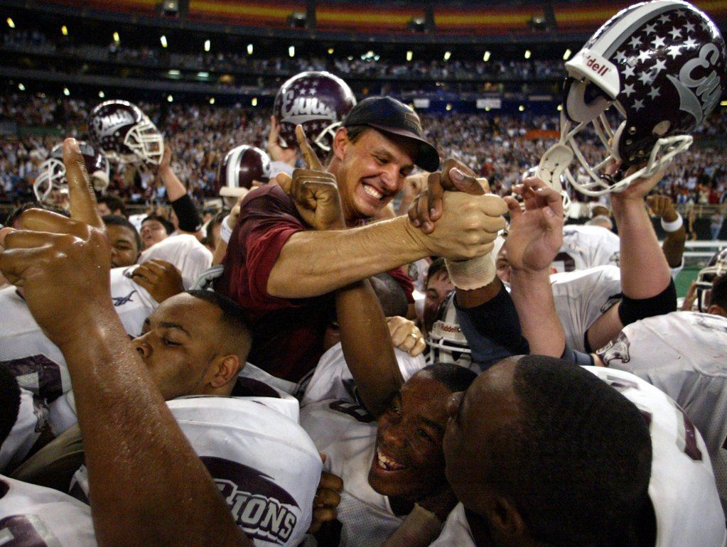 Ennis head coach Sam Harrell is lifted by his players after beating Bay City  21-0 for the 4A Div II UIL state football championship at the Houston Astrodome Saturday.