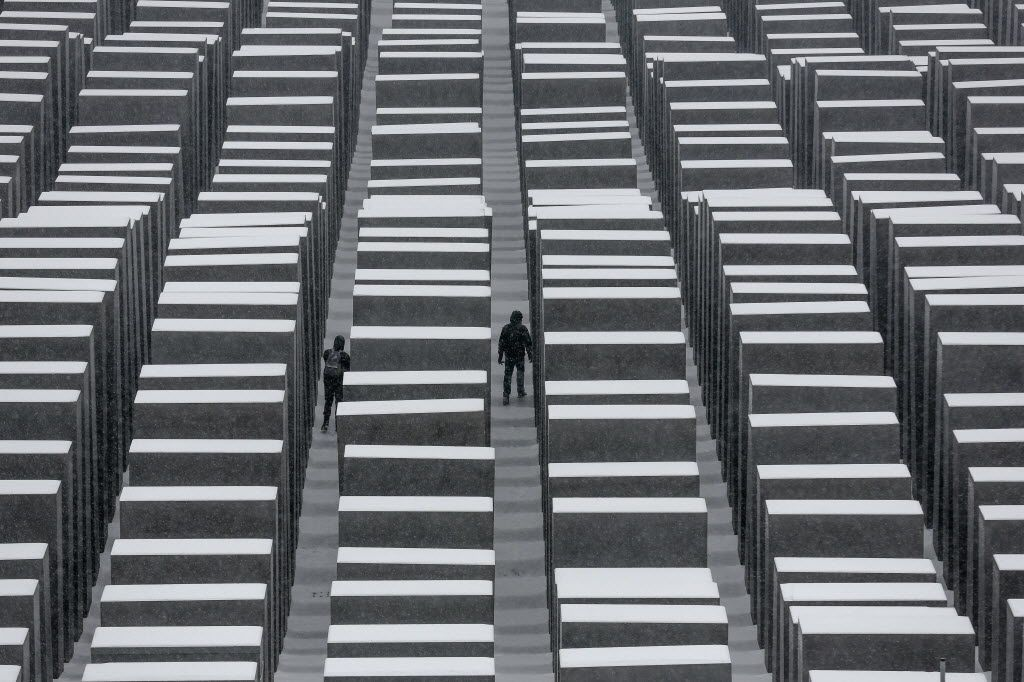 Visitors walk explore the snow-covered Holocaust Memorial at the International Holocaust Remembrance Day in Berlin, in January, 2014.