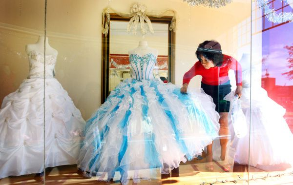 Juanita Martinez adjusts awindow display at Anali's Novias Y Quincianeras on Jefferson Boulevard in North Oak Cliff. Several small business owners said they think the change in policy will hurt them more than larger retailers.